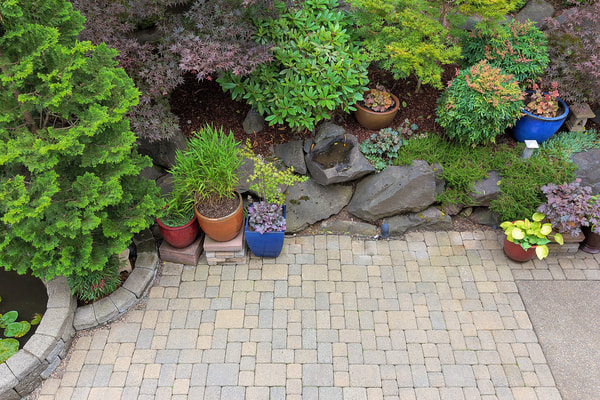 Landscaping performed on a back yard. Stone tiles were installed into a backyard in Burnaby.